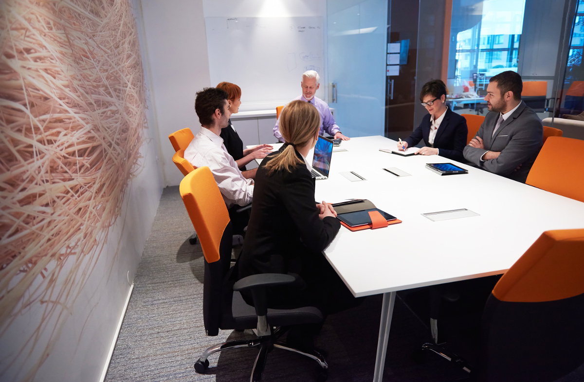 Business Team Seated Around Meeting Table in Modern Office