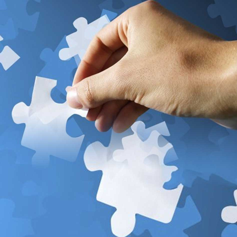 Hand Holding Puzzle Pieces on Blue Background